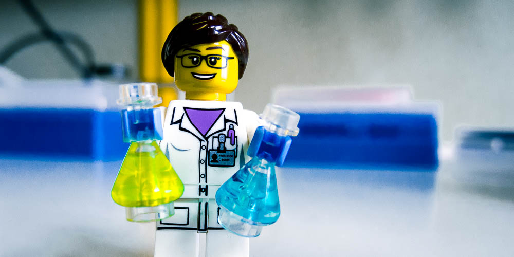 lego scientist with reagent bottles in his hands